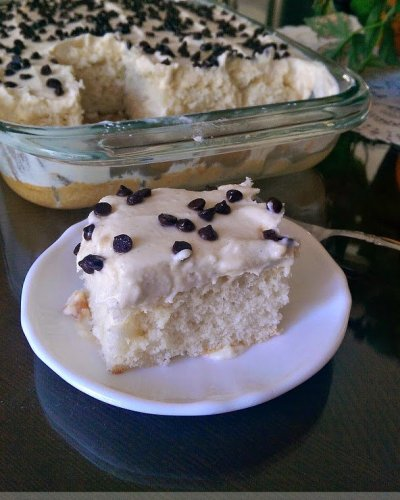 Cannoli Poke Cake - This is a super moist white cake topped with cannoli filling frosting and mini chocolate chips.| Persnickety Plates