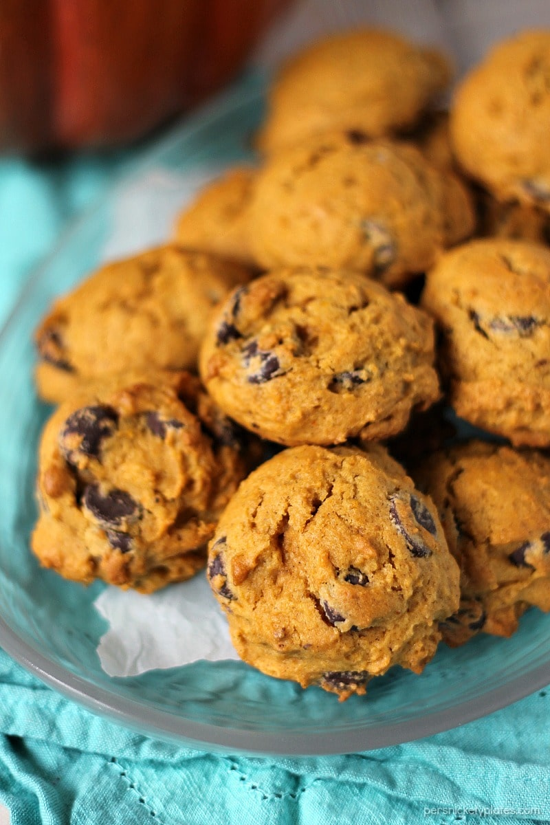 vertical shot of pumpkin chocolate chip cookies on clear platter with wax paper and teal napkin