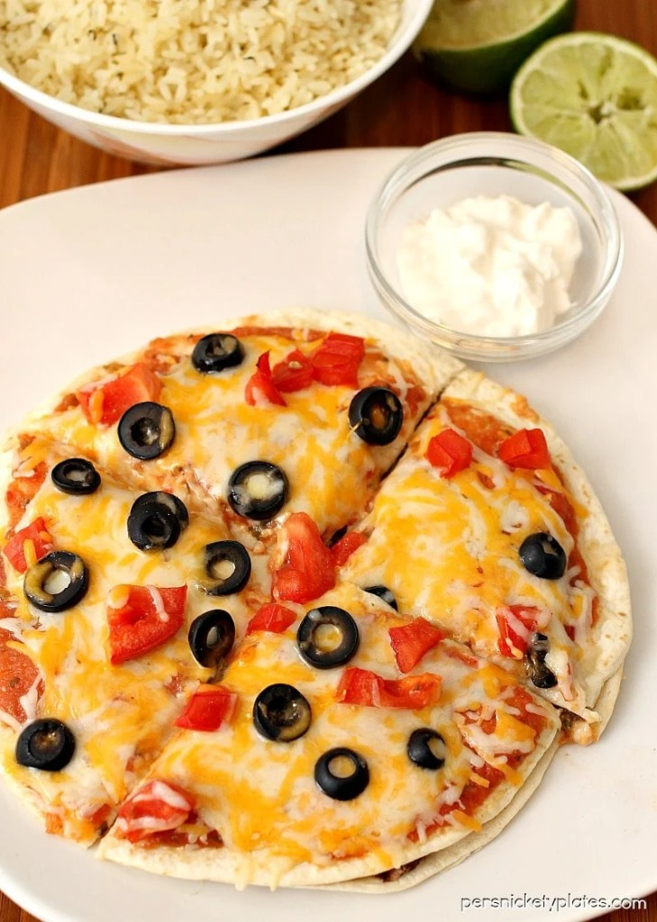 mexican pizza with a side of sour cream on a white plate
