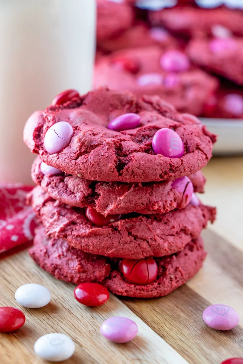 stack of 4 red velvet cake mix cookies surrounded by pink M&Ms