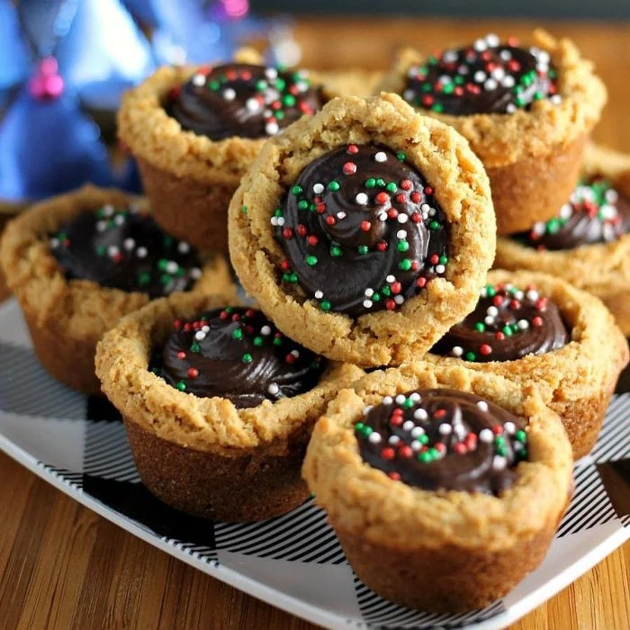 stack of peanut butter cookie cups filled with chocolate & topped with christmas sprinkles
