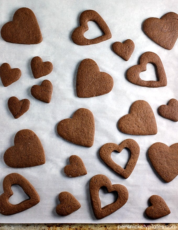 Chocolate Frosted Valentine Cookies start with a simple chocolate roll-out cookie base, frosted and sprinkled for Valentine's Day!   www.persnicketyplates.com