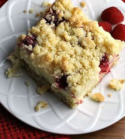 Raspberry Cream Cheese Crumb Cake is layered with a creamy cheesecake , fresh raspberries, and topped with a cruchy streusel topping. Perfect for brunch or dessert! | Persnickety Plates