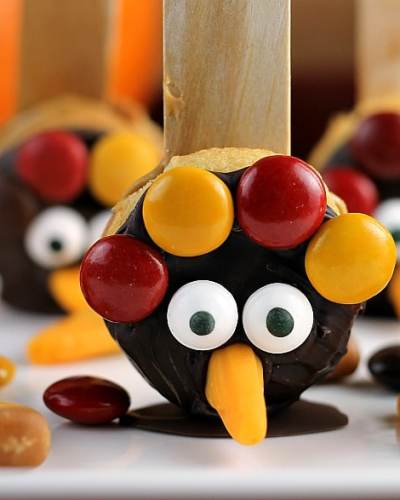Vanilla Wafer Thanksgiving Turkeys are Nilla Wafers sandwiched together with peanut butter, dipped in chocolate, and decorated with fall colored M&Ms, candy corn, and googly eyes. So fun for the kids and festive for the Thanksgiving table! | Persnickety Plates
