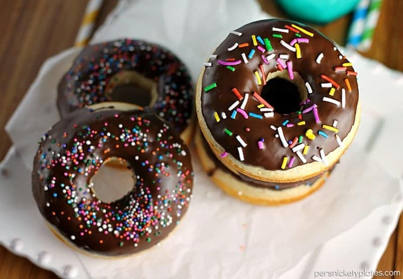 Chocolate Glazed Baked Cake Donuts covered in sprinkles. Homemade donuts are probably easier to make than you think and you can save a trip to the donut shop! | www.persnicketyplates.com