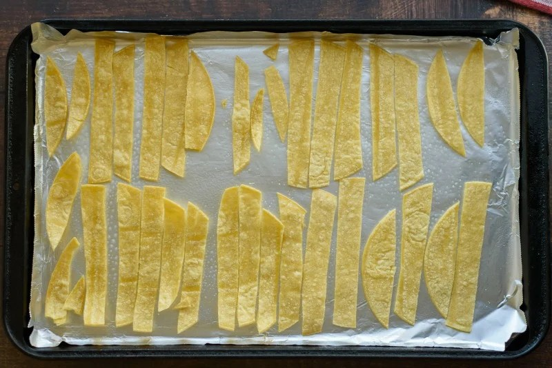 sliced corn tortillas on a baking sheet for tortilla strips
