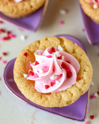 Valentine Sugar Cookie Cups are a simple, semi-homemade treat that you can whip up in no time! A sugar cookie base filled with pink frosting and topped with Valentine sprinkles. | www.persnicketyplates.com