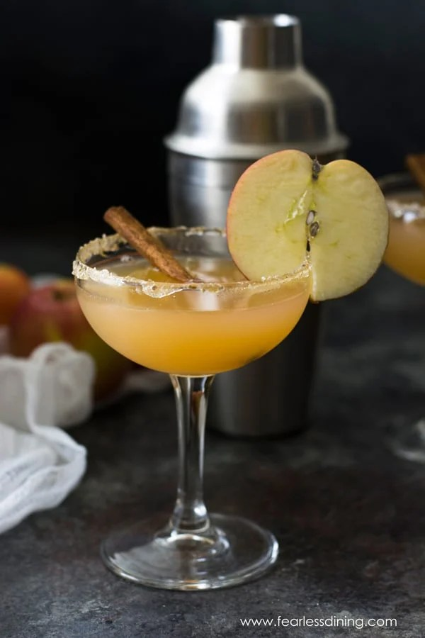 bourbon cider in a martini glass with an apple garnish