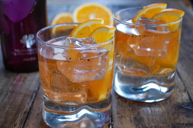two fig vodka cocktails with orange garnish