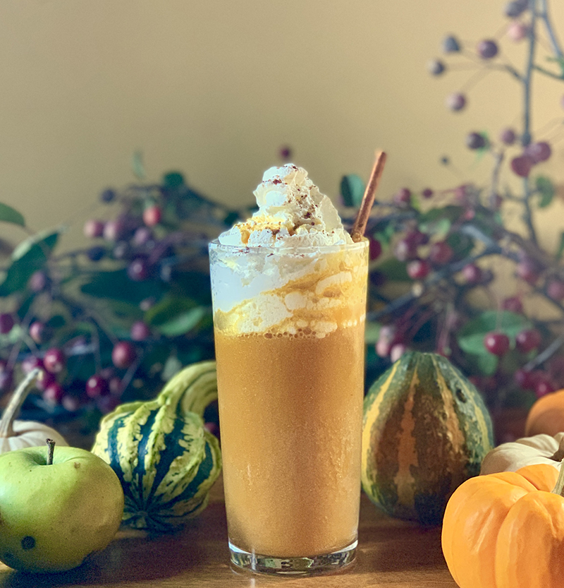 pumpkin spice cooler cocktail surrounded by ghords