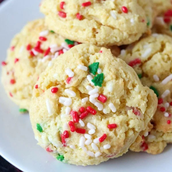 close up of cookie with christmas sprinkles on white plate