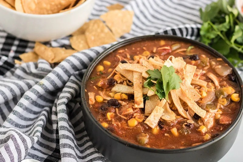 black bowl of chicken tortilla soup with a dish towel