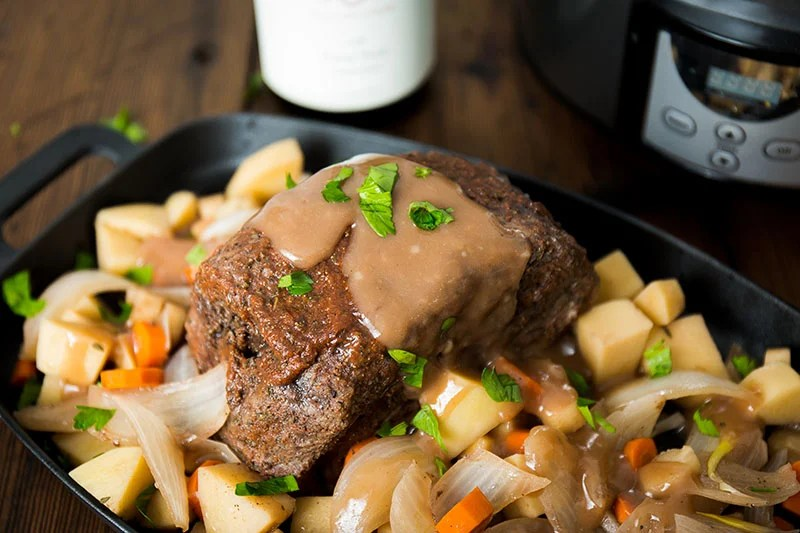 pot roast topped with gravy over vegetables