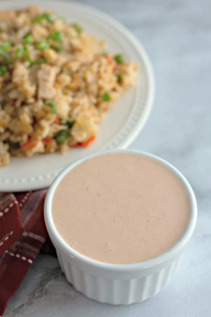white cup of yum yum sauce in front of fried rice