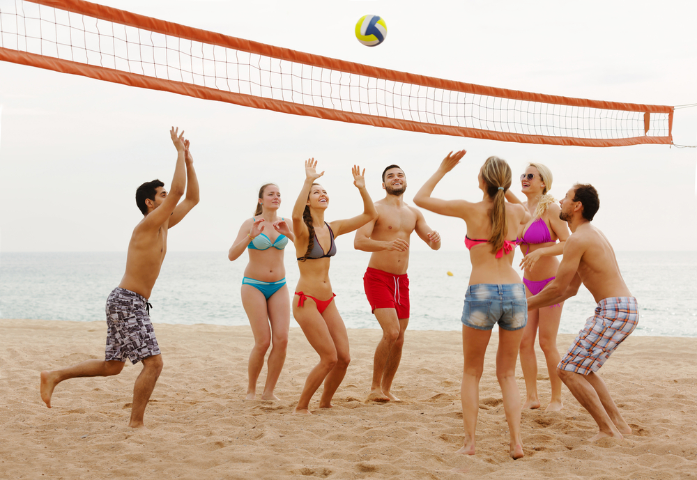 A group of Spring Break vacationers stay active at the resort by playing a fun game of beach volleyball.