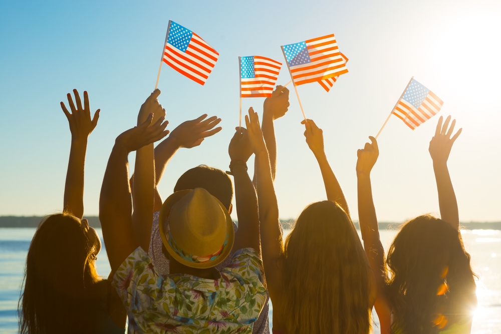 A group of friends waving flags on the beach in celebration of a healthy Memorial Day with Personal Trainer Food.