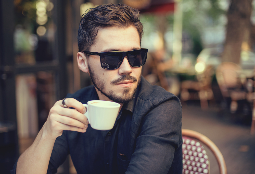 A handsome man at a cafe wears sunglasses as he sips on his coffee.