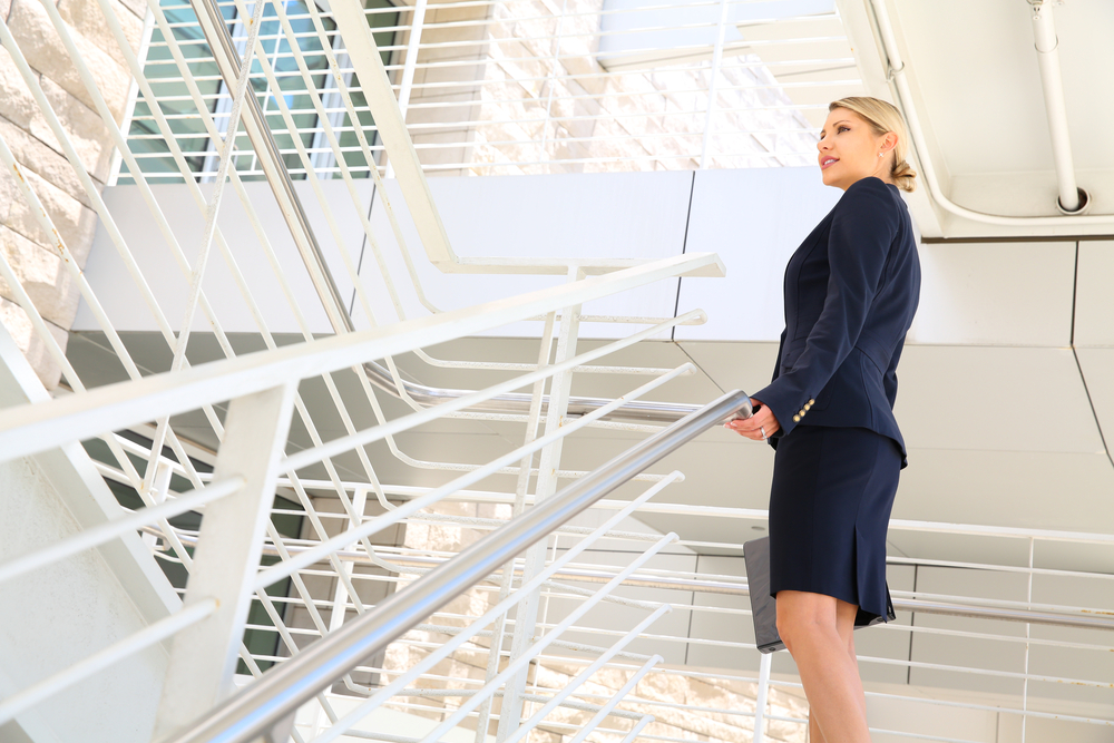 A woman climbs the stairs at her office to lose weight and stay slim.