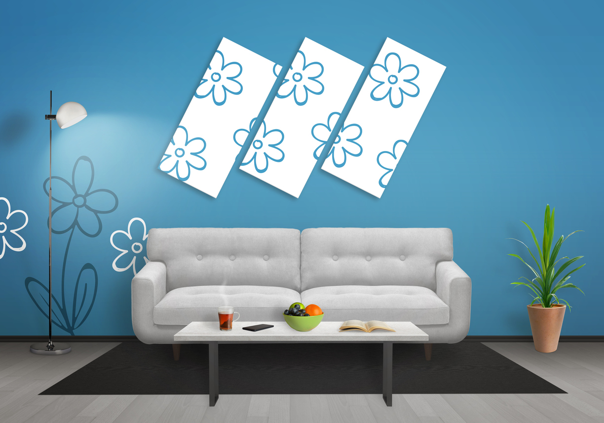 Flowers on foam art canvas in living room. Blue wall with flower wallpaper and gray wooden floor. Sofa, table, lamp and plant in room.