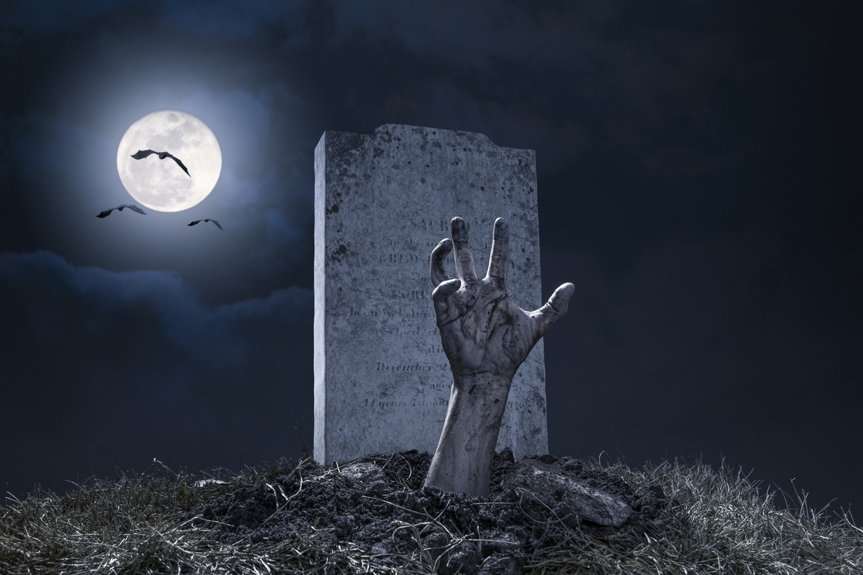 A zombie hand bursting through the grave in a graveyard on Halloween night under a full moon with vampire bats.