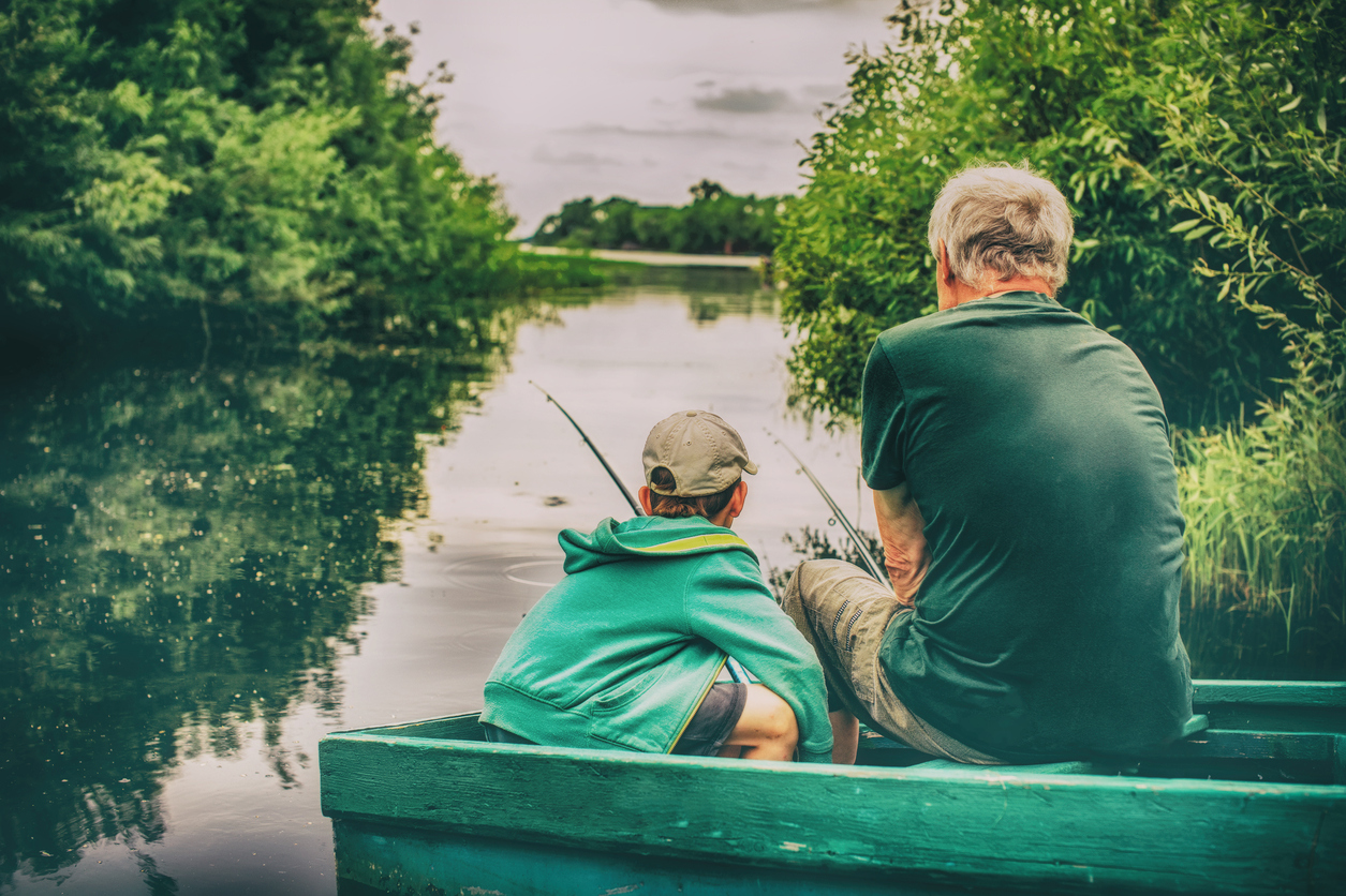 Boy and grandfather sitting in a boat with a fishing rod.