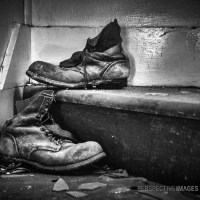 Put Your Best Boot Forward - Discarded miners boots sit on the stair well of an abandoned house.