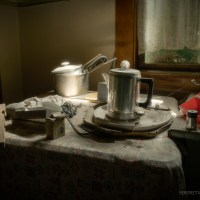 Tea Time - Dust covered pots and a kettle sit illuminated by a single light beam.