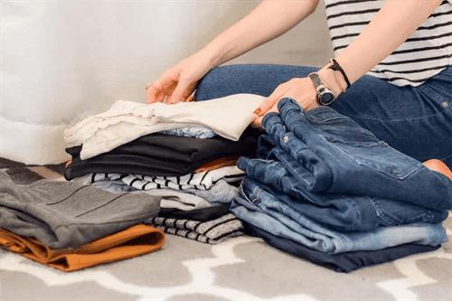 たくさんの洋服を片付ける女性