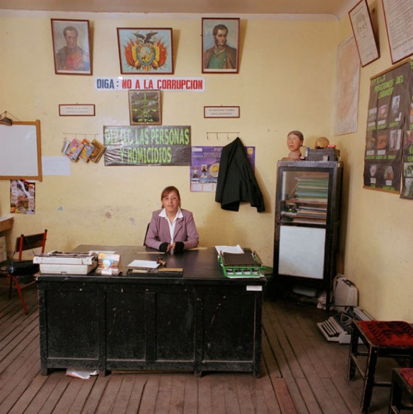 """Bolivia, bureaucracy (police), 2005. Marlene Abigahit Choque (1982), detective at the the Homicide Department of the Potosi police. The department has only broken typewriters, no computer, no copy machine, not even telephone. It shares a car with the Vice Squad: """"If there is no petrol in the car, we have to buy it from our own money. If the car is gone, we take the bus. We have to pay the tickets ourselves."""" The head on the cupboard to the right is used to make witnesses of murder cases show where the bullets went in or out.Monthly salary: 920 bolivianos (euro 102, US$ 114)."""