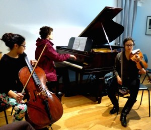 Caitlin and Audrey work with Sean on 'expanding' his piano piece into a chamber work