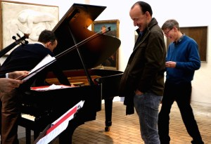 Richard Causton, centre with fellow composer Jeremy Thurlow. Roderick Chadwick prepares the piano for 'Seven States of Rain' and an Amati scroll waits for action! Kettle's Yard 27 4 14 (Photo Malene Skaerved)