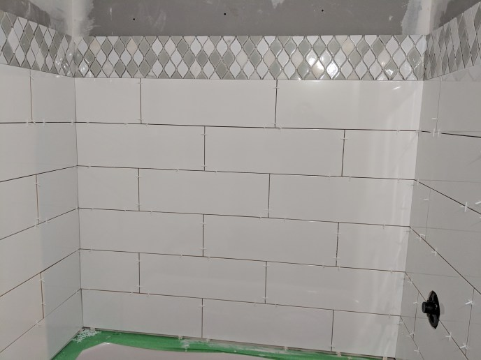 Tiles with accent piece in the process of being installed