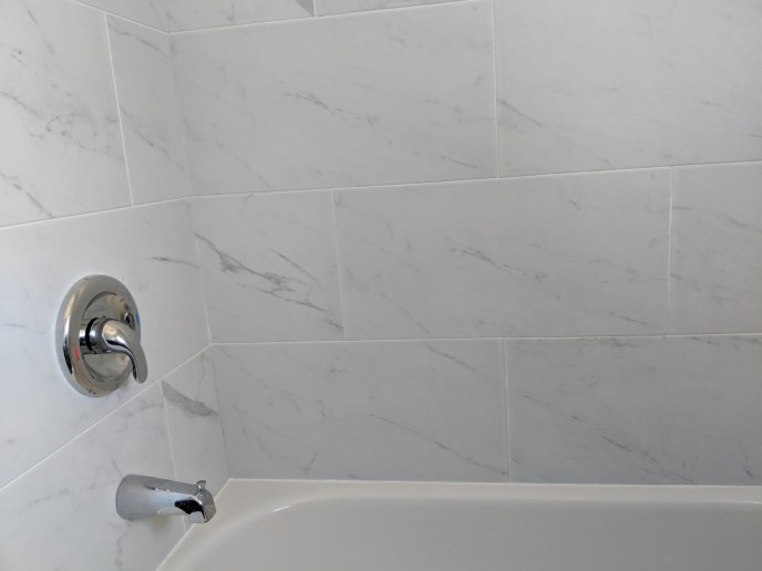 Small bathroom reno, new tub, shower valve and tiles with grout installed