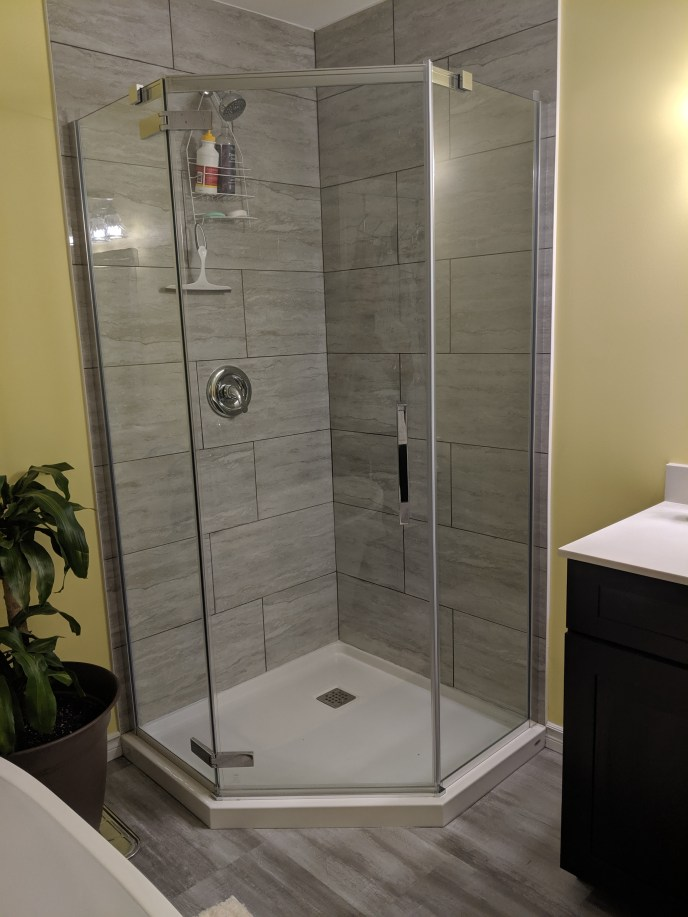 New shower, vanity, tub, and floor installed in an enlarged bathroom