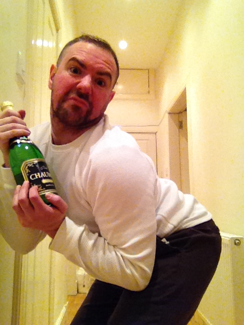 Close up of Christmas shopping blog poster posing with a bottle of wine and his bum sticking out