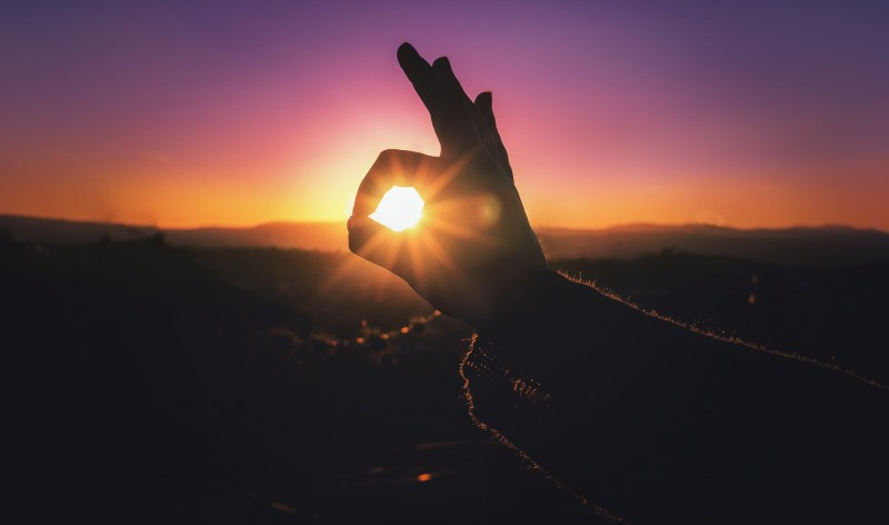 Close up of a thumb and forefinger making an okay sign against a sunset background