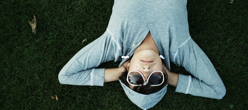 Image of man with shades lying face up on grass
