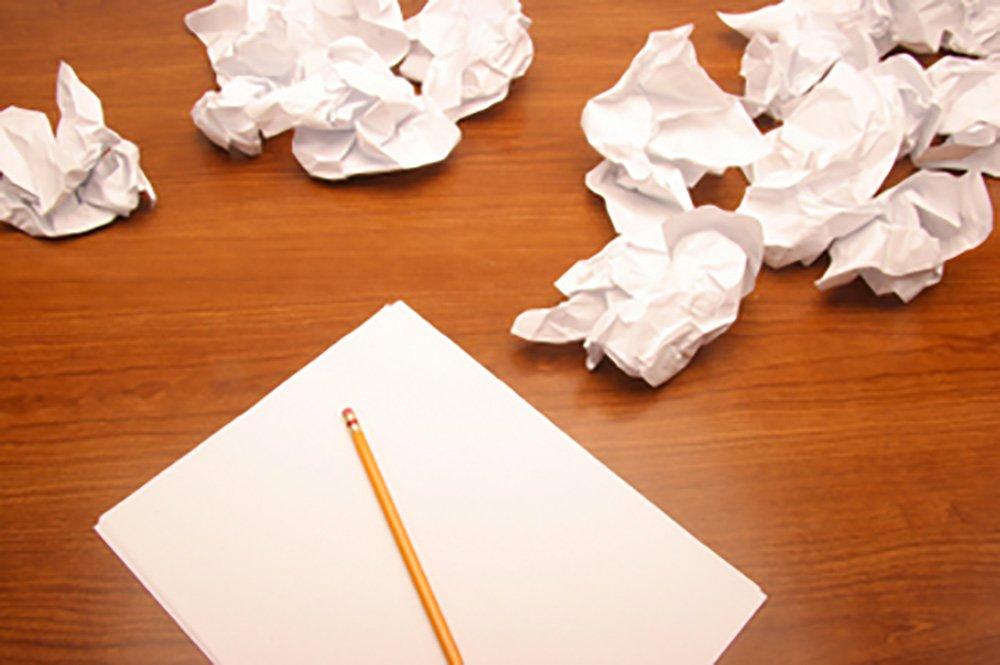 Une page blanche et un crayon au côté de papiers froissés