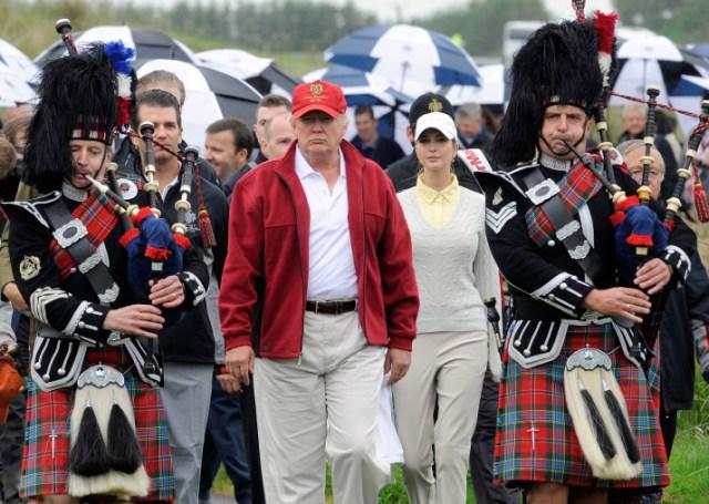 taipan AS Donald Trump (C) diikuti oleh bagpipers Skotlandia saat ia bekerja di lapangan secara resmi membuka baru multi-juta pound LINK nya Trump International Golf Course di Aberdeenshire, Skotlandia, pada 10 Juli 2012. dimulai pada bulan Juli 2010 empat tahun setelah rencana yang diajukan. PHOTO AFP / Andy Buchanan (pinjaman Foto harus Andy Buchanan / AFP / Getty Images baca)