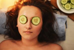 a woman with two slices of cucumbers on her eyes