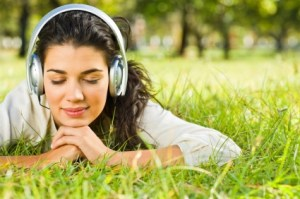 Closeup portrait of beautiful young woman laying on grass and listening to music with headphones