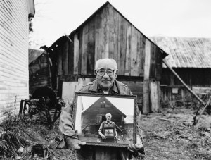 Fred Tuttle holding a photo of his father holding a photo of his father and grandfather