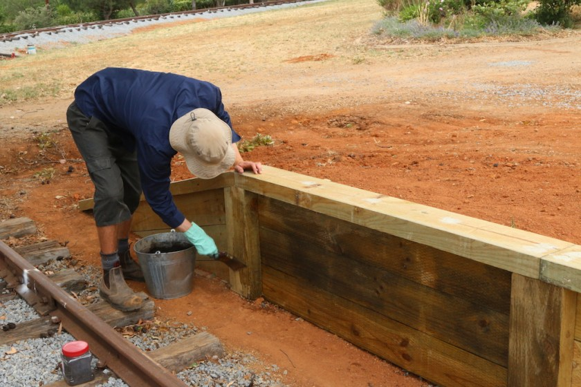 Image 2016.5103: The platform coping has been completed, along with the sloping ends and now Josh ages the timberwork. (Thursday 8/12/2016)