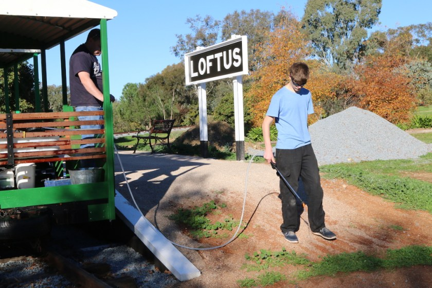 Image 2017.2760: The hose is of sufficient length to allow spraying a little away from the rail track area. Rhys attacks weeds already growing on Loftus platform as Ben looks on in a supervisory roll.