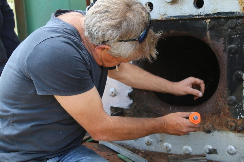 Image 2017/4812: Having removed the firebox sliding doors from the Fowler, Bill checks for any pitting around the Firehole door.