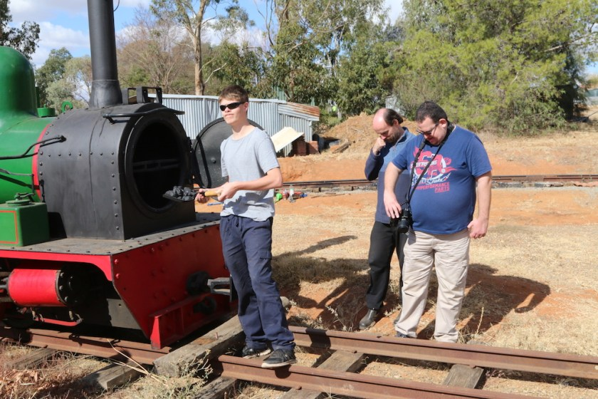 """Image 2018.0717: When a couple of mates turned up from Victoria on Sunday 29th April for a brief inspection of Pete's Hobby Railway, I got Rhys to show them how he fires the Hunslet steam engine… """"well, if the smoke comes out of the chimney/funnel, the fire must be at this end of the locomotive."""" Many, many years ago, I remember seeing a leading Sydney hobby shop actually display a then British Railways 4F type tender-type 0-6-0 locomotive with the tender coupled to the smokebox! Being a good sport, Rhys agreed to the pose, although he has been trained as to where the coal should go!"""