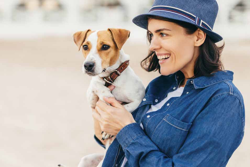 Picture of a woman in blue coat holding a dog