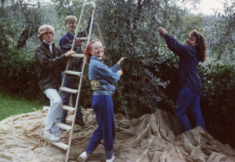 1990 - Long ago, I went to school in Florence, Italy and got to pick olives like in the old days. Note my jeans cinched at the ankles and my denim jacket with an adobe house painted on the back. So chic.