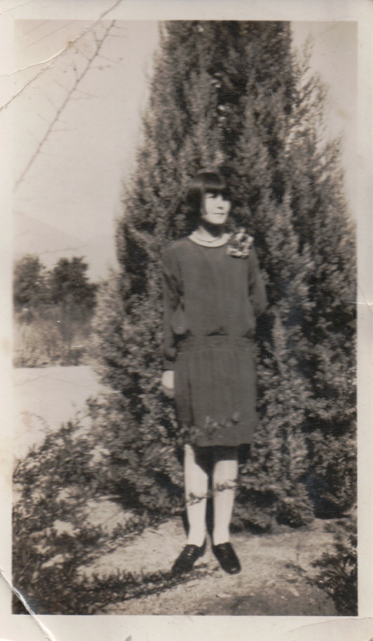 A young woman from the late-1920s standing next to a tree.