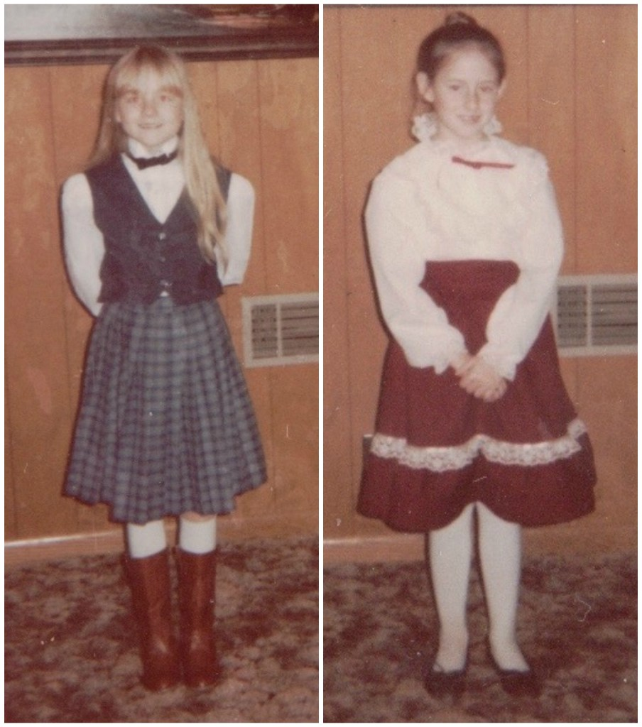 Two girls dressed in fashions from the early 80s - one more feminine, the other more masculine, both dressed in skirts.